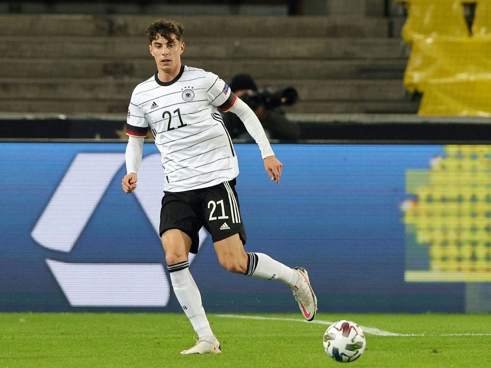 Kai Harvertz steht hinter Bundestrainer Joachim Löw